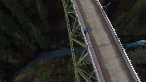 An-aerial-over-a-man-walking-on-a-steel-suspension-bridge-over-the-Skokomish-River-in-Washington-USA