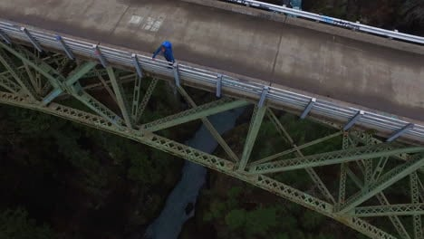 An-aerial-over-a-man-standing-on-a-steel-suspension-bridge-over-the-Skokomish-River-in-Washington-USA