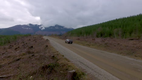 Beautiful-aerial-of-a-4WD-truck-driving-through-the-Cascades-Wilderness-in-Washington-USA