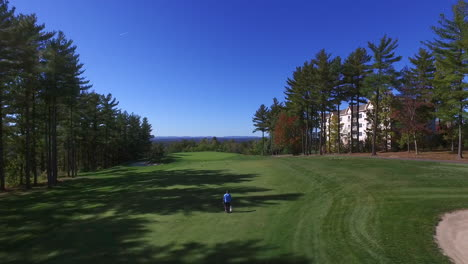 Aerial-shot-of-a-man-walking-on-a-golf-course-on-a-beautiful-day