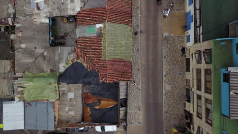 Aerial-establishing-shot-looking-straight-down-of-a-red-tile-roofed-neighborhood-and-streets-in-Bogota-Colombia