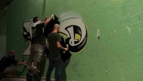 Time-lapse-shot-of-graffiti-being-sprayed-on-a-wall-by-taggers