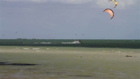 People-engage-in-the-fast-moving-sport-kite-boarding-along-a-sunny-coast