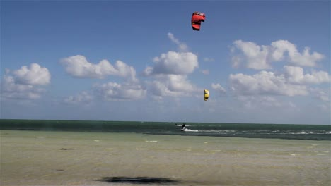 People-engage-in-the-fast-moving-sport-kite-boarding-along-a-sunny-coast-2