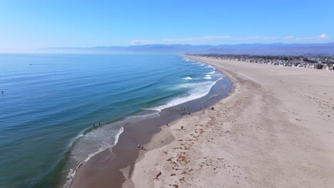 An-Excellent-Aerial-Shot-Shows-People-Walking-Along-The-Surf-On-A-Beach-In-Oxnard-California