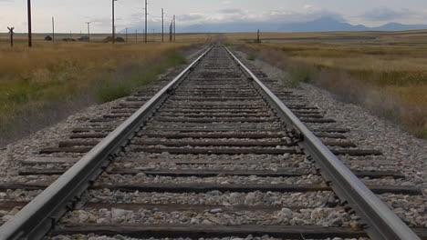 Railroad-Tracks-Stretch-Across-A-Grassy-Plain-Into-The-Horizons