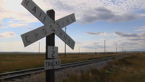 A-Railroad-Crossing-Sign-Rests-Stand-Next-To-Old-Train-Tracks