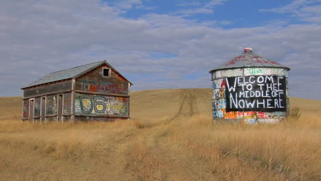 An-Old-Abandoned-House-And-Water-Tower-With-Graffiti-Stand-In-An-Open-Prairie