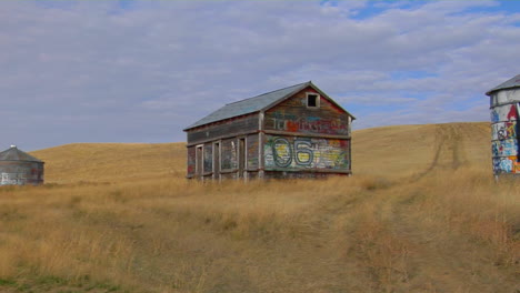 An-Old-Abandoned-House-And-Water-Tower-With-Graffiti-Stand-In-An-Open-Prairie-1