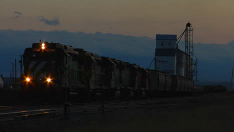 A-Freight-Train-Passes-A-Grain-Silo-At-Dusk