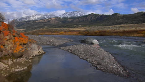 A-Small-Stream-Runs-Beneath-Snow-Covered-Mountains-In-Yellowstone-National-Park