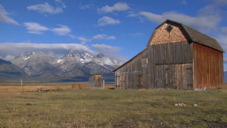 Eine-Alte-Scheune-Steht-Auf-Einem-Feld-Mit-Der-Großen-Teton-bergkette-Im-Hintergrund