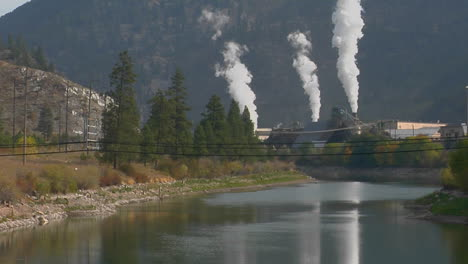 Smoke-Comes-Billowing-Out-Of-A-Factory-Along-A-Waterway