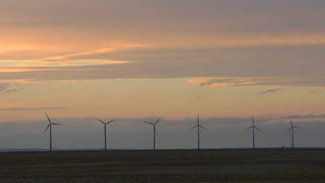 A-Line-Of-Windmills-Are-Silhouetted-Against-A-Golden-Sky