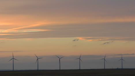 A-Line-Of-Windmills-Are-Silhouetted-Against-A-Golden-Sky-1