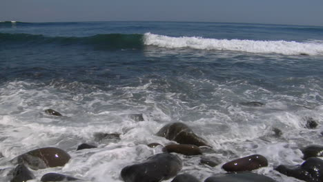 Waves-Washing-Over-Small-Smooth-Rocks-On-The-Beach