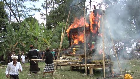 Los-Hombres-Usan-Palos-Largos-Para-Pinchar-Una-Pira-Funeraria-Durante-Una-Ceremonia-De-Cremación-En-Bali-