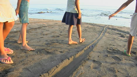 Bali-Children-Play-A-Game-Rolling-Bottle-Caps-Down-The-Beach