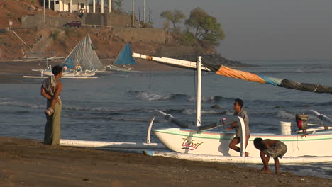 Boys-Push-A-Catamaranstyle-Fishing-Boat-To-Shore-In-Indonesia