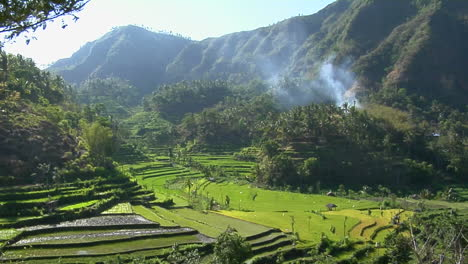 Mist-Seeps-Down-A-Mountainside-Above-Green-Terraced-Rice-Paddies