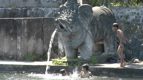 Boys-Jump-Into-The-Water-Of-A-Giant-Stone-Fountain-In-Bali-Indonesia