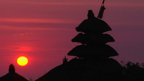 The-Pura-Tanah-Lot-Temple-Stands-In-Silhouette-Against-A-Glowing-Sky