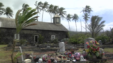 Wind-Blows-Over-A-Heavily-Decorated-Grave-On-A-Tropical-Island