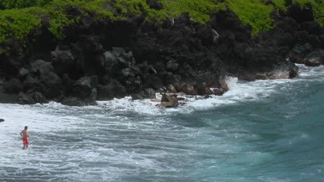 Un-Hombre-Lucha-Contra-Un-Gran-Oleaje-En-Una-Playa-De-Arena-Negra-En-Hawaii
