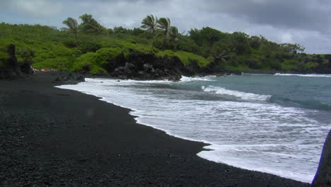 Waves-Roll-Into-A-Black-Sand-Beach-In-Hawaii