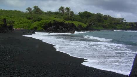 Las-Olas-Ruedan-Hacia-Una-Playa-De-Arena-Negra-En-Hawaii
