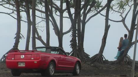 Liebhaber-Stehen-Vor-Einem-Perfekten-Meerblick-Mit-Einem-Ford-Mustang-Cabrio-Im-Vordergrund