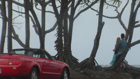 Liebhaber-Stehen-Vor-Einem-Perfekten-Meerblick-Mit-Einem-Ford-Mustang-Cabrio-Im-Vordergrund-1