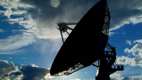 A-Satellite-Dish-Moves-In-Time-Lapse-And-Is-Silhouetted-Against-The-Sky