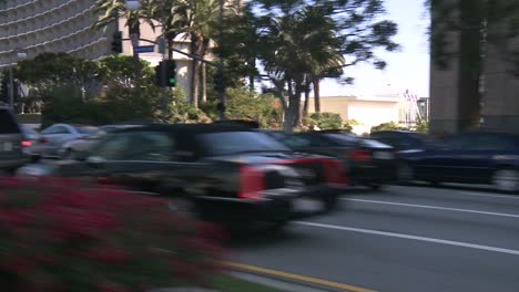 Ein-Auto-Fährt-Eine-Straße-In-Der-Jahrhundertstadt-Los-Angeles-Entlang-Wie-Durch-Die-Hintere-Scheibe-Schräg-Gesehen