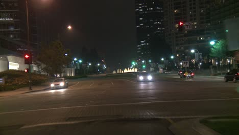 A-Car-Travels-Along-A-Street-At-Night-In-Century-City-Los-Angeles-As-Seen-Through-The-Rear-Window-2