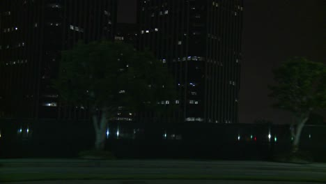 A-Car-Travels-Along-A-Street-At-Night-In-Century-City-Los-Angeles-As-Seen-Through-The-Side-Window