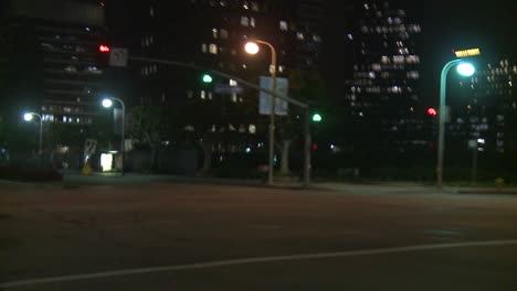 A-Car-Travels-Along-A-Street-At-Night-In-Century-City-Los-Angeles-As-Seen-Through-The-Rear-Window-At-An-Angle