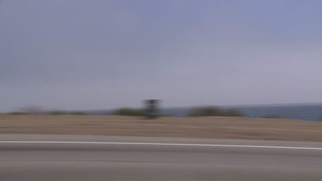 A-Car-Travels-Along-Pacific-Coast-Highway-As-Seen-Through-The-Side-Window-3