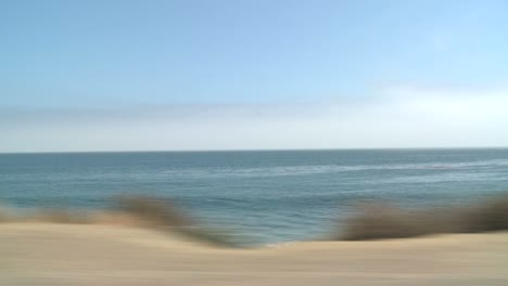 A-Car-Travels-Along-Pacific-Coast-Highway-As-Seen-Through-The-Side-Window-9