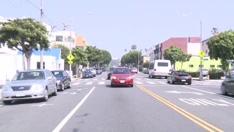 A-Car-Travels-Along-A-Street-In-Venice-California-As-Seen-Through-The-Rear-Window