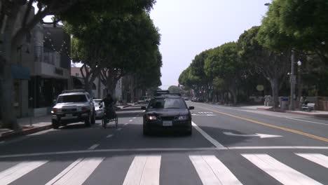 A-Car-Travels-Along-A-Street-In-Santa-Monica-California-As-Seen-Through-The-Rear-Window