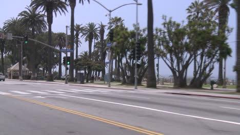 Un-Automóvil-Viaja-A-Lo-Largo-De-Una-Calle-Junto-Al-Mar-En-Santa-Mónica-California-Como-Se-Ve-A-Través-De-La-Ventana-Trasera-En-ángulo