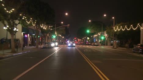 Un-Automóvil-Viaja-Por-Una-Calle-De-Noche-En-Santa-Mónica-California-Visto-A-Través-De-La-Ventana-Trasera-3