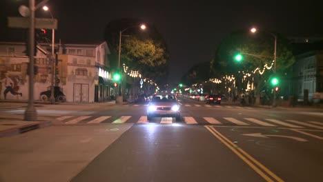 Un-Automóvil-Viaja-Por-Una-Calle-De-Noche-En-Santa-Mónica-California-Visto-A-Través-De-La-Ventana-Trasera-4