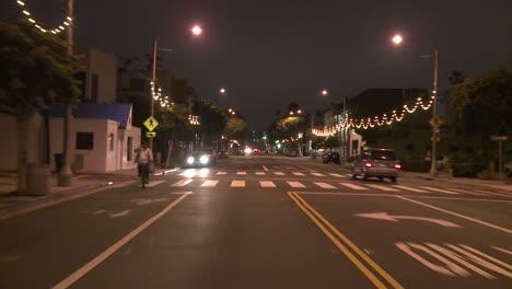 Un-Automóvil-Viaja-Por-Una-Calle-De-Noche-En-Santa-Mónica-California-Visto-A-Través-De-La-Ventana-Trasera-5