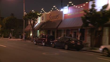 A-Car-Travels-Along-A-Street-At-Night-In-Santa-Monica-California-As-Seen-Through-The-Rear-Window-At-An-Angle