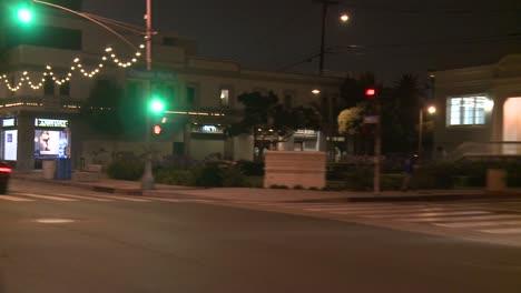 A-Car-Travels-Along-A-Street-At-Night-In-Santa-Monica-California-As-Seen-Through-The-Rear-Window-At-An-Angle-1