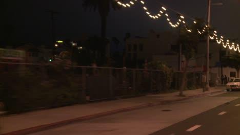 A-Car-Travels-Along-A-Street-At-Night-In-Santa-Monica-California-As-Seen-Through-The-Rear-Window-At-An-Angle-3