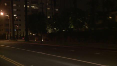 Un-Automóvil-Viaja-Por-Una-Calle-De-Noche-En-Santa-Mónica-California-Visto-A-Través-De-La-Ventana-Trasera-En-Un-ángulo-4