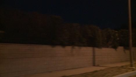 Ein-Auto-Fährt-Nachts-Eine-Kurvenreiche-Straße-In-Los-Angeles-Kalifornien-Entlang-Gesehen-Durch-Die-Heckscheibe-In-Einem-Winkel-Von-1